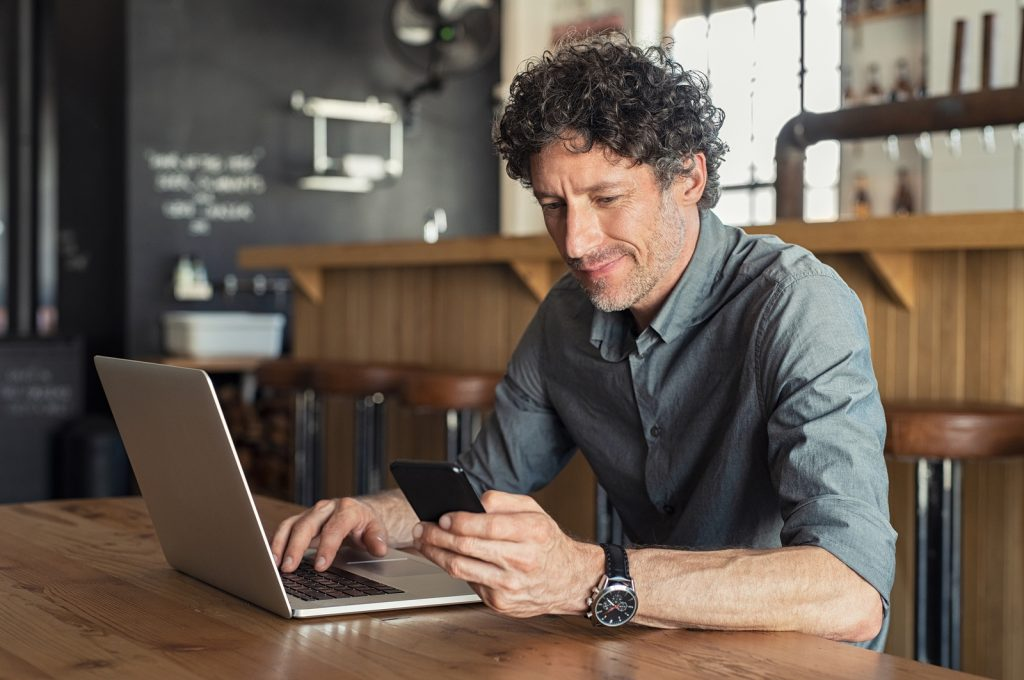 Happy mature business man sitting at cafeteria with laptop